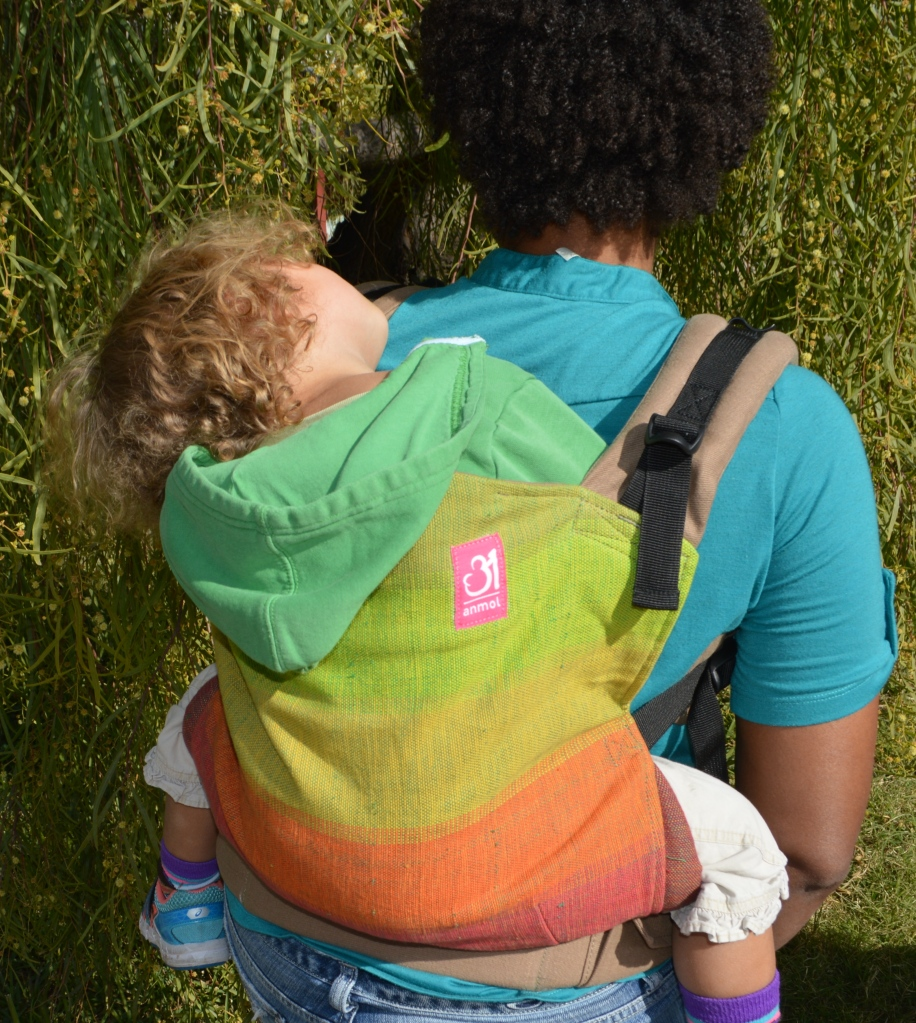 Medium brown Momma wears light brown blond curly haired sleeping toddler on her back in a grad handwoven soft structured carrier with colors from red to orange to yellow to lime green to grass green against a n orange weft. The carrier has a khaki colored waistband and shoulder straps.