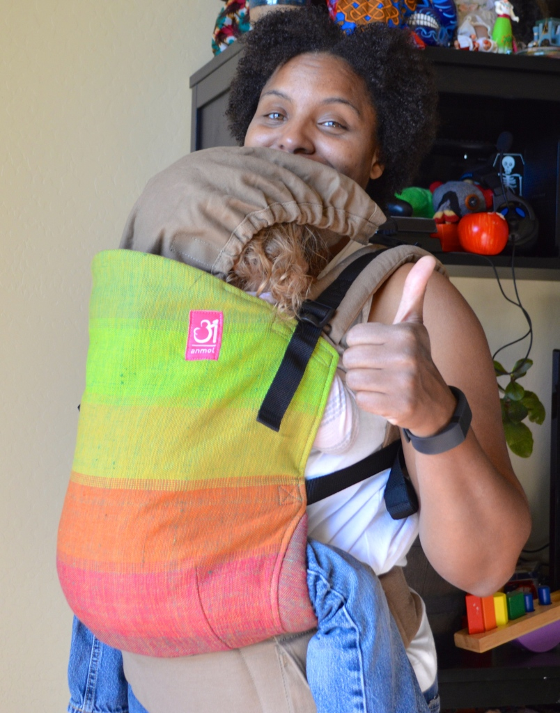 Medium brown Momma wears light brown blond curly haired sleeping toddler on front in a grad handwoven soft structured carrier with colors from red to orange to yellow to lime green to grass green against a n orange weft. The carrier has a khaki colored waistband and shoulder straps.