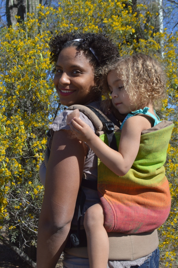 Medium brown Momma wears light brown blond curly haired toddler on her back in a grad handwoven soft structured carrier with colors from red to orange to yellow to lime green to grass green against a n orange weft. The carrier has a khaki colored waistband and shoulder straps. Baby is holding a large piece of rose quartz in her hand and the creosote bushes are in bloom with yellow flowers behind them.