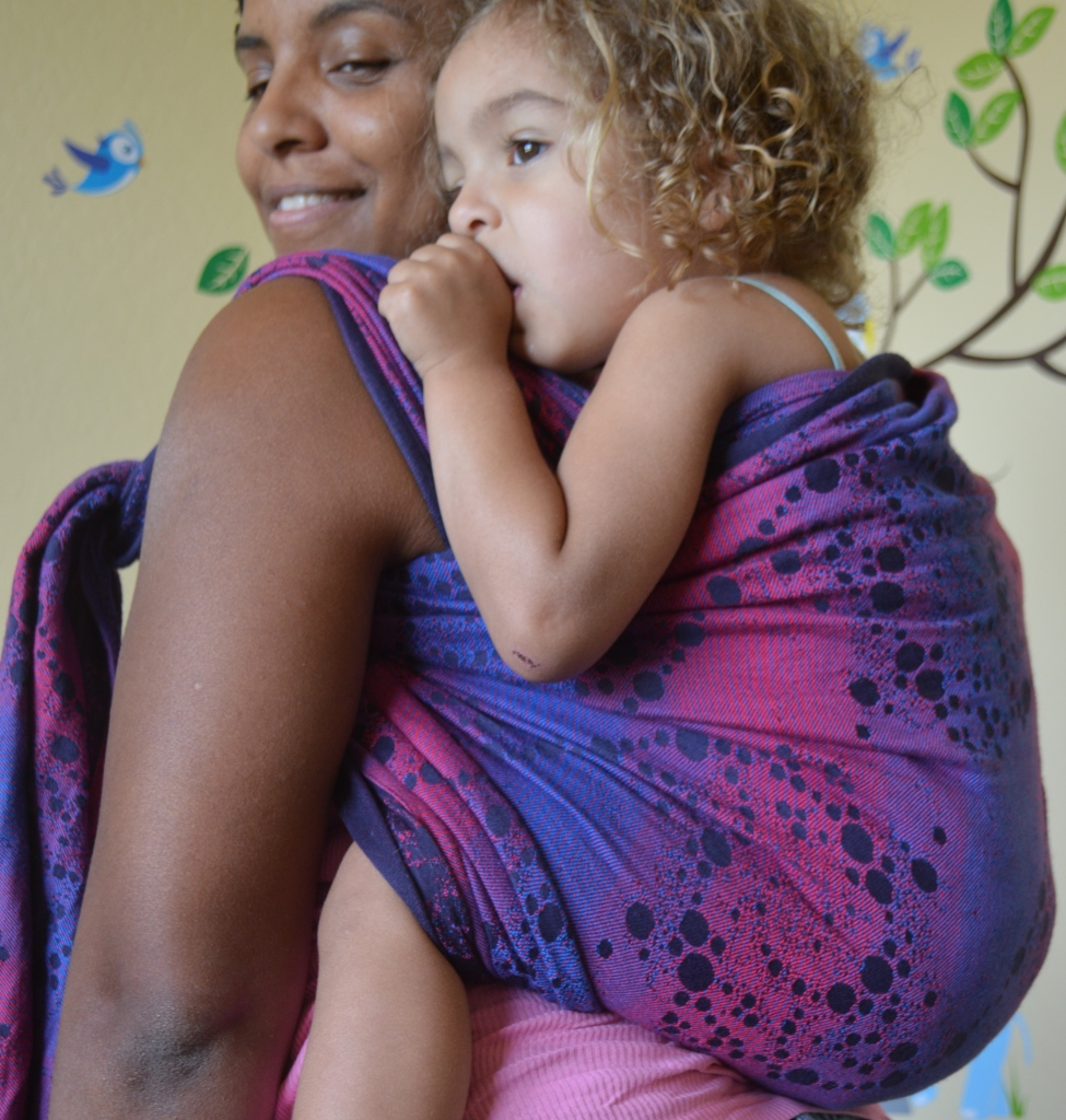 Medium brown Momma with curly hair wears light brown, blond haired sleeping toddler in back carry in a magenta, purple, and navy blue swap with galaxy spirals