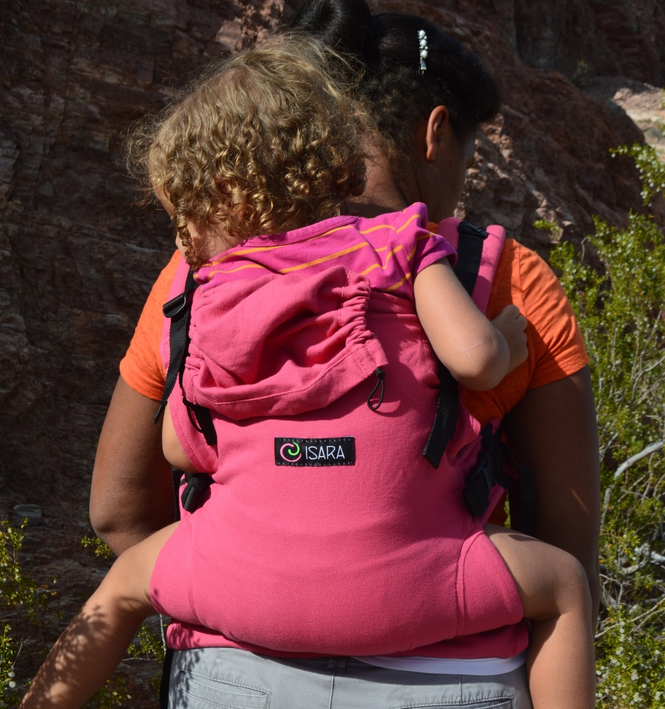 Medium brown Momma wears light brown blond curly haired toddler on her back in a pink soft structured carrier