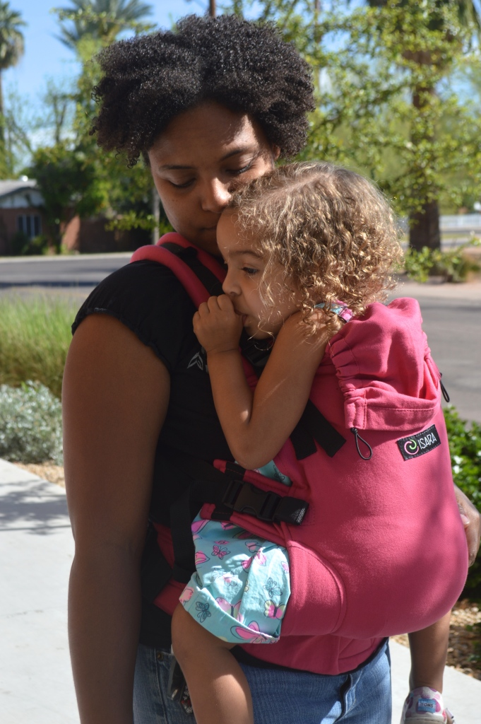 Medium brown Momma wears light brown blond curly haired toddler on front in a pink soft structured carrier