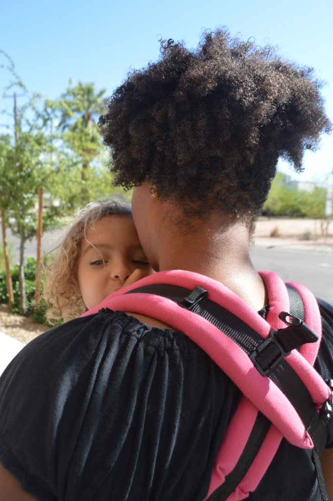 Image shows the back of medium brown curly haired momma with blong, curly haired toddler sucking her thumb in a front carry with straps crossed.