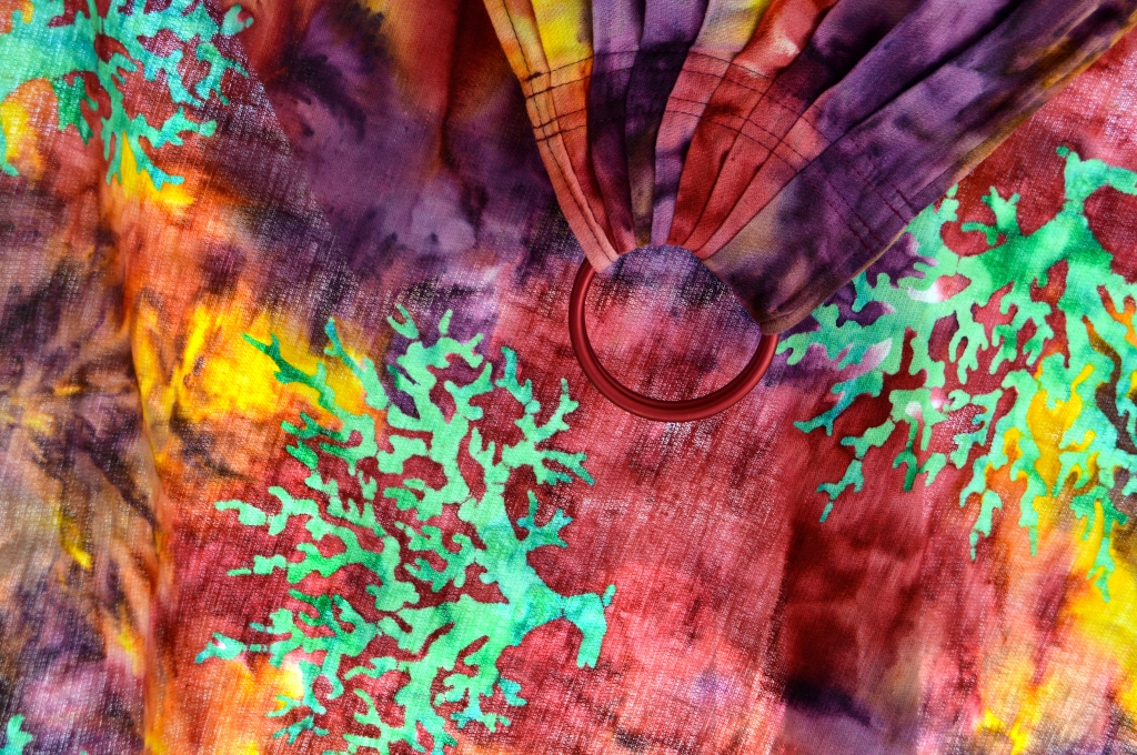 Macro image of a ring sling with perfect pleated shoulder in red, purple, and yellow tie dye with slightly embossed vibrant pale green branching trees