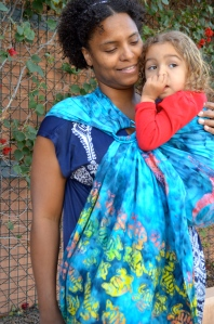 Baby is seen picking her nose with her thumb while looking over her shoulder. Medium brown Momma with Natural curly hair wears light brown, blond curly haired toddler on her hip in a tie-dye blue ring sling with sea turtles on the tail