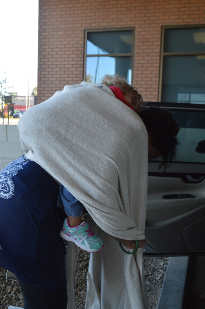 Woman stands, obscured by a white woven wrap with a sleeping toddler on her back