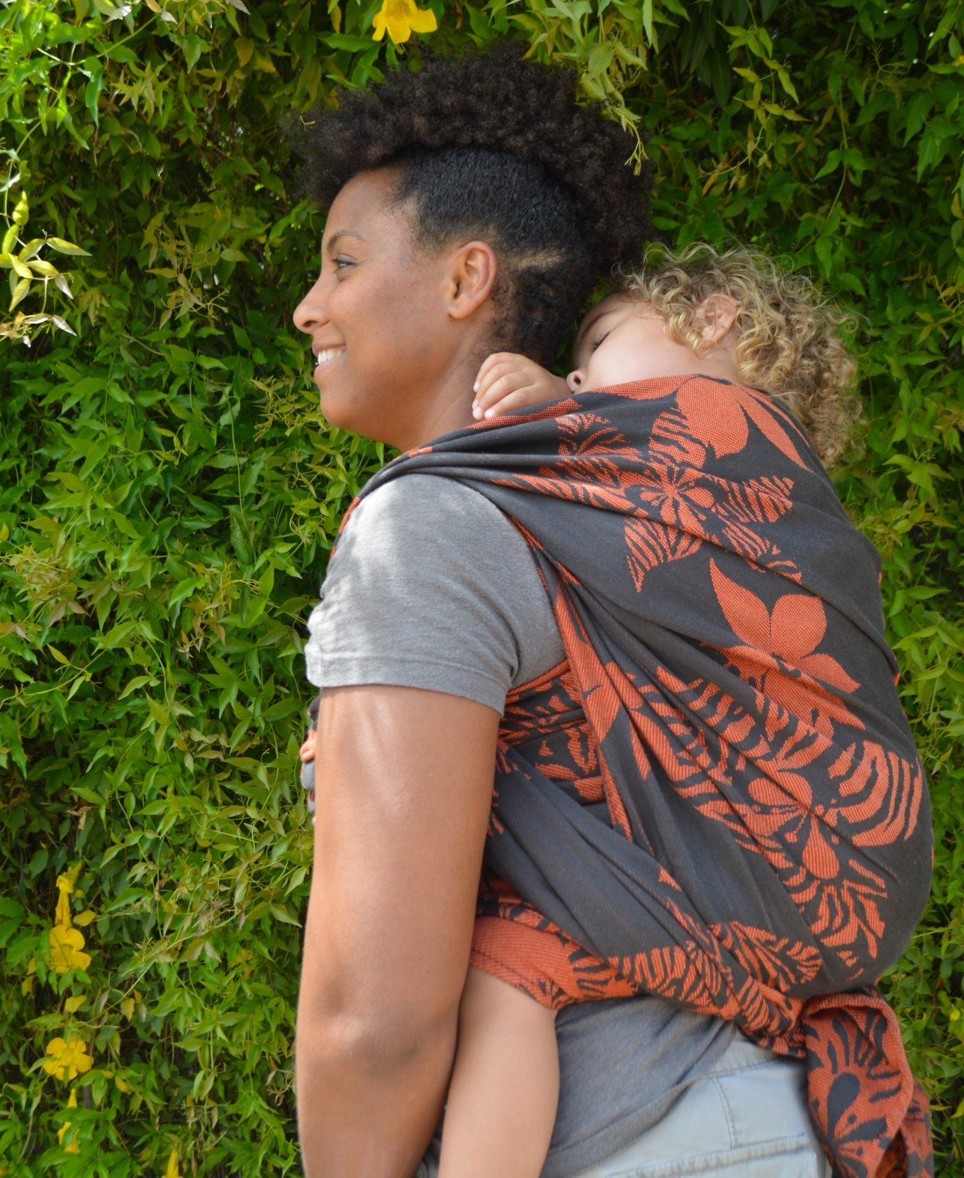 Momma wears blond curly haired toddler on her back in a black wrap with orange flowers. Baby is sleeping and Momma is smiling, looking off in the diistance