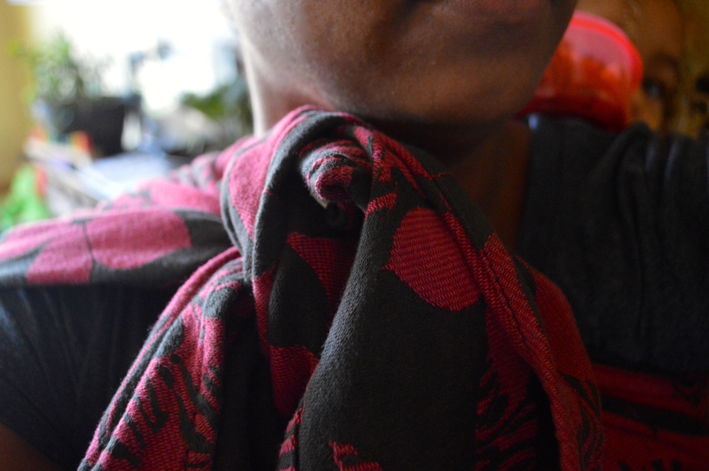 Closeup image of a woven wrap with contrasting flowers in magenta and black are tied in a large fist sized knot at the wearer's shoulder pressing on the neck and chin.