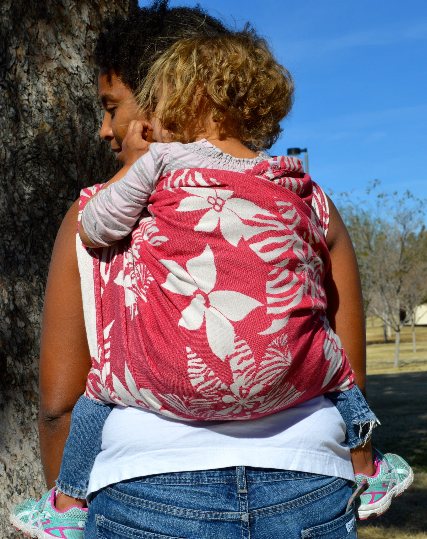 Momma wears blond curly haired toddler on her back in a magenta wrap with white flowers.