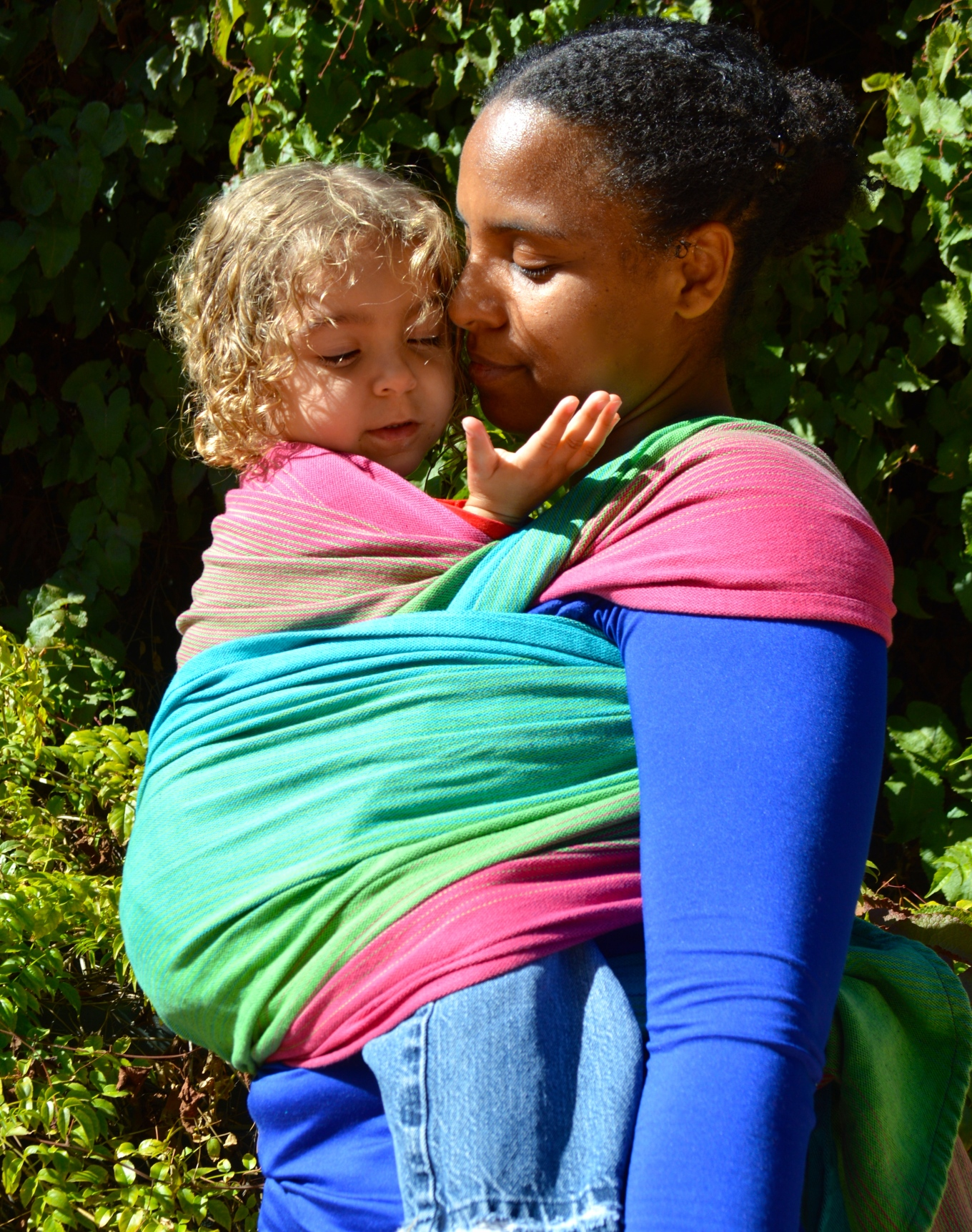 Momma gives kisses to toddler worn in a front carry in magenta, green, pink, and turquoise wrap.