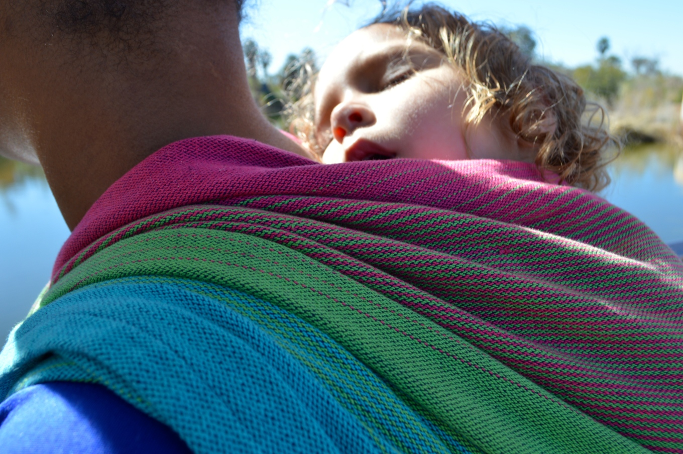 close up shot of sleeping baby face on Momma's shoulder with the wrap pleated at her shoulder