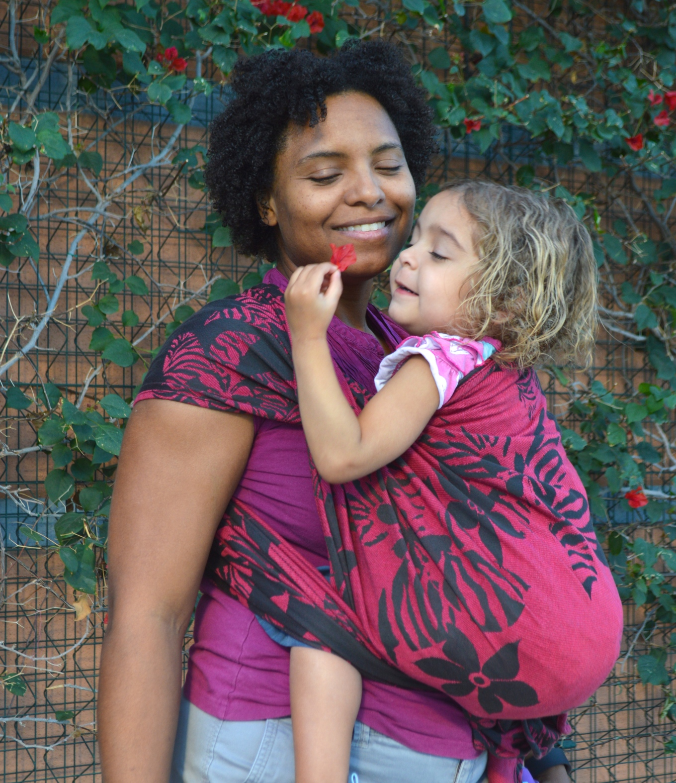 Momma smiles at baby holding magenta flowers in a front carry in a magenta wrap with black flowers