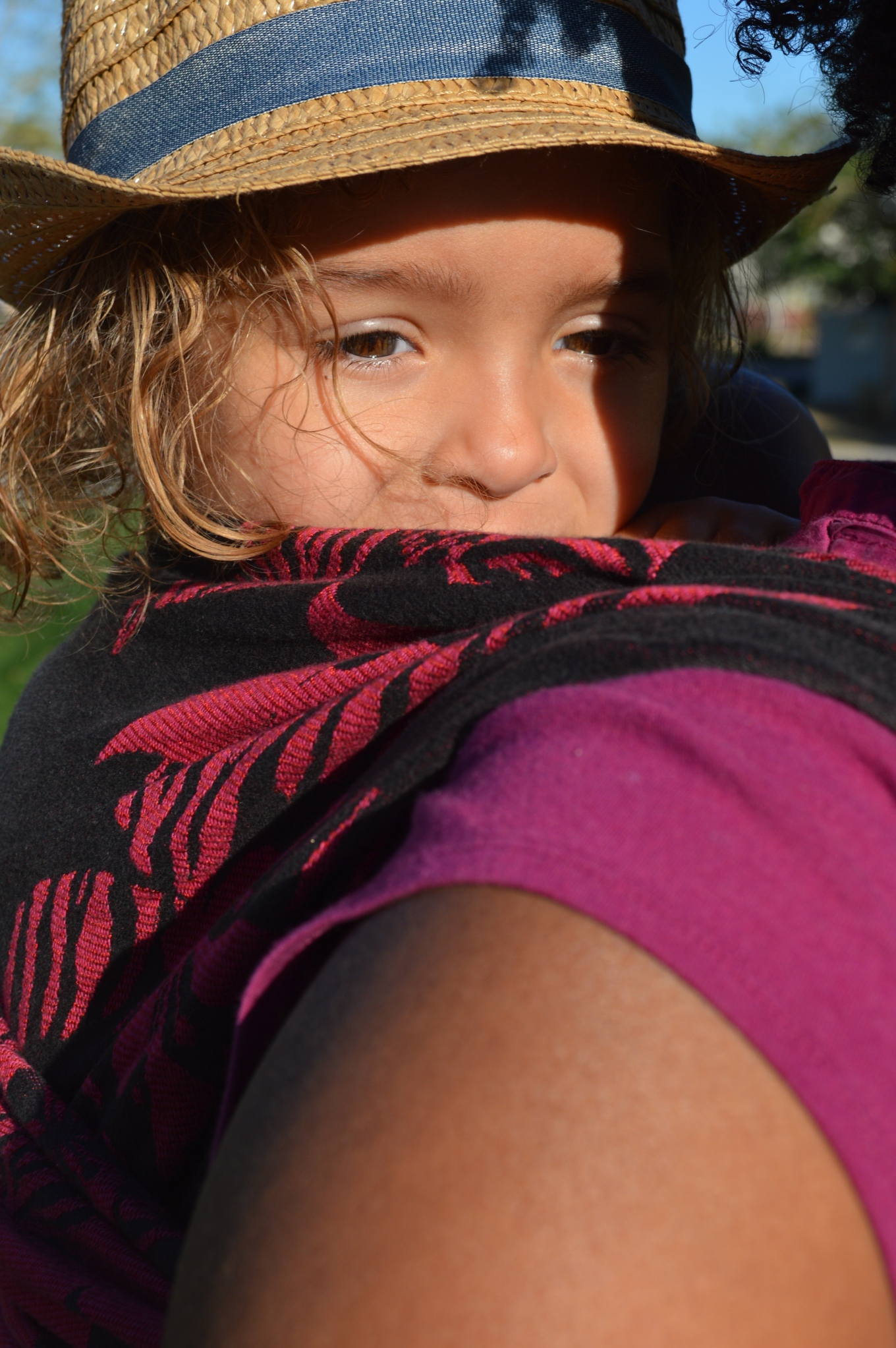 Close up shot of baby's face looking out toward the camera wearing a straw fedora hat. Baby is on Momma's back in a black wrap with magenta flowers
