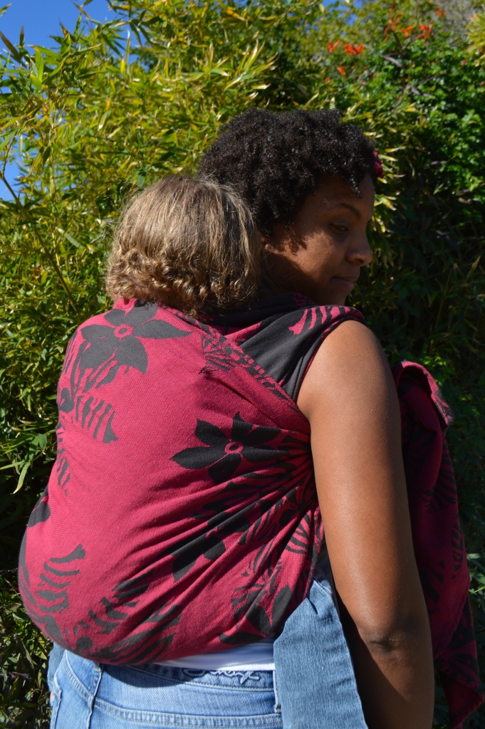 Momma looks back over her shoulder at baby on her back in a magenta wrap with black flowers