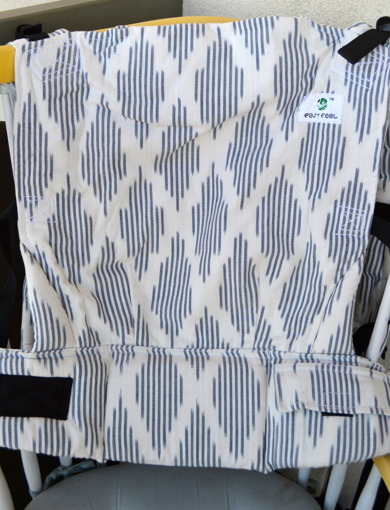 Image shows close up of the carrier showing a dominant white background with navy blue diamond Ikat pattern over the body, waistband, and shoulder straps of the carrier