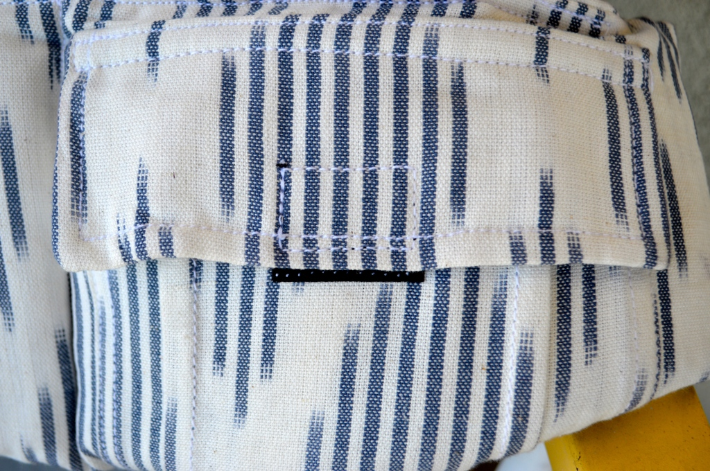 Image shows a close up on the pocket on the waistband. Closes with a velcro and is white and navy blue Ikat diamond design