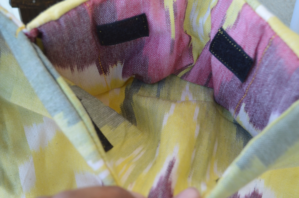 Image shows yellow, pink, and white pattern of the hood storage pouch inside the top of the carrier body