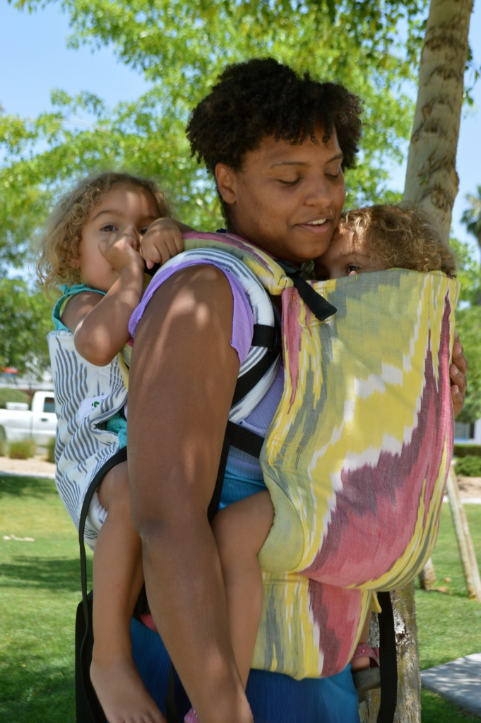 Image shows a medium brown momma wearing a light brown, blond haired toddler on her back in a gray and white diamond print soft structured carrier. The baby worn on her front is hiding, arms tucked inside of the pink, yellow, and white soft structured carrier