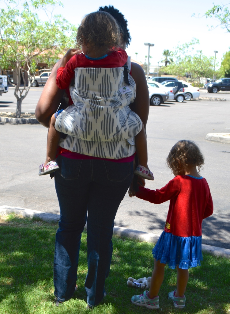 Image shows a back view of a toddler worn in a gray and white diamond print toddler sized soft structured carrier. The woman holds another toddler's hand as they near the street