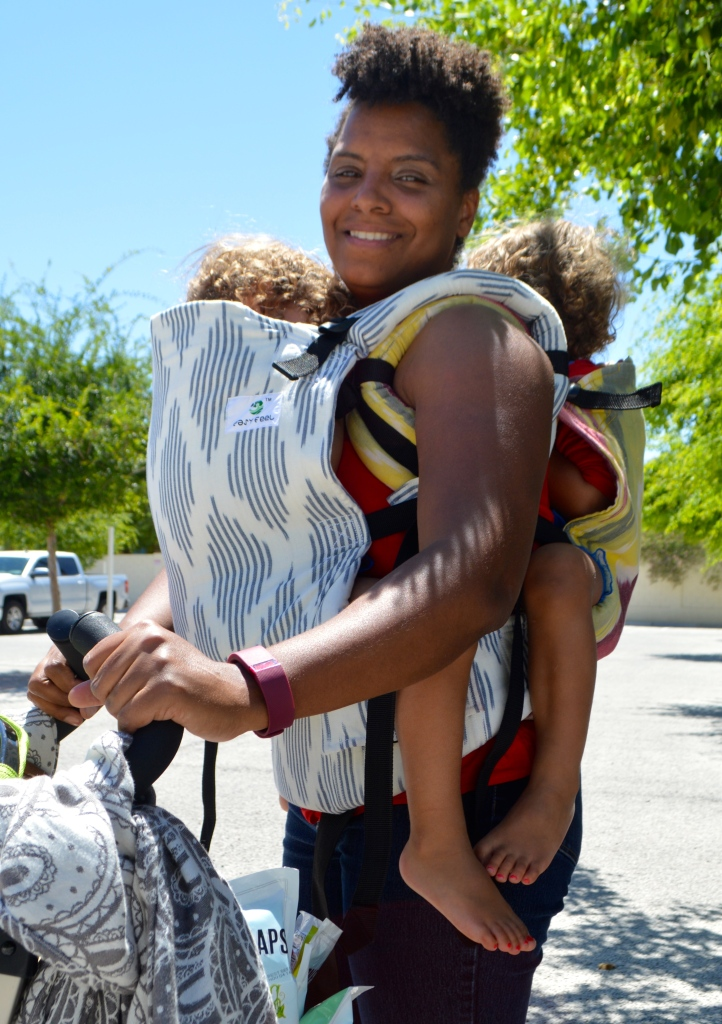 Image shows a woman smiling into the camera wearing twin toddlers one in front in a navy blue and white soft structured carrier and the other in a yellow pink and white soft structured carrier as she pushes the stroller full of groceries.