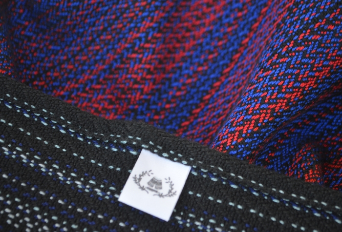 Closeup detail of the weave pattern and colors in the hand woven wrap. The colors transition from black with silver gray stripes to rich red and vibrant blue. The color transitions back to black and gray on the end of the rails