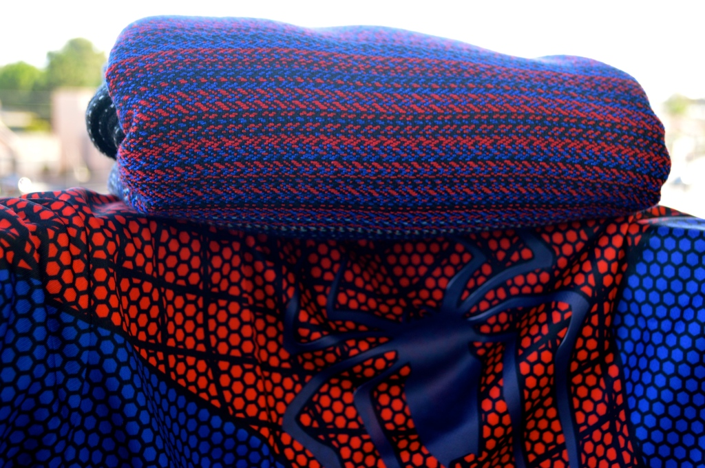 Image shows the black, red, and blue wrap folded neatly atop a red and blue shirt with blue spider-man logo in the center.