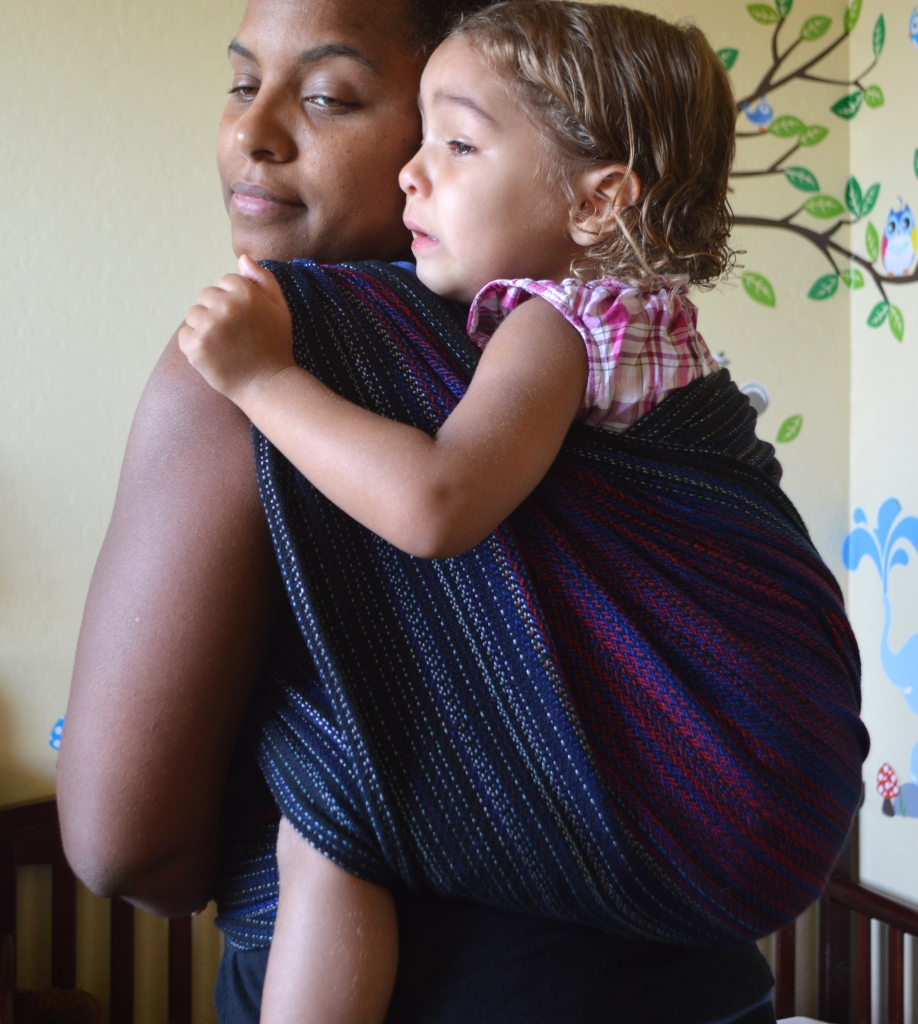 Image of a medium brown woman looking over her shoulder wearing a light brown, blond haired toddler on her back in a black, red, and blue wrap