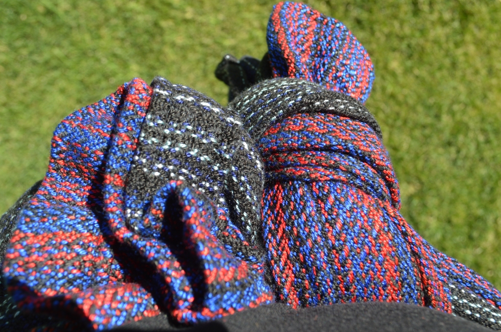 Closeup detail of the weave pattern and colors in the hand woven wrap. The colors transition from black with silver gray stripes to rich red and vibrant blue. The color transitions back to black and gray on the end of the rails. The image is from the point of view of the wearer, looking down at a large knot