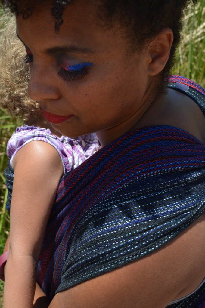 Close up view, over the shoulder of the wearer showing the black, red, and blue of the wrap on her shoulder and the baby's arm in view. Her eye shadow is red and blue glitter with long black eyelashes.