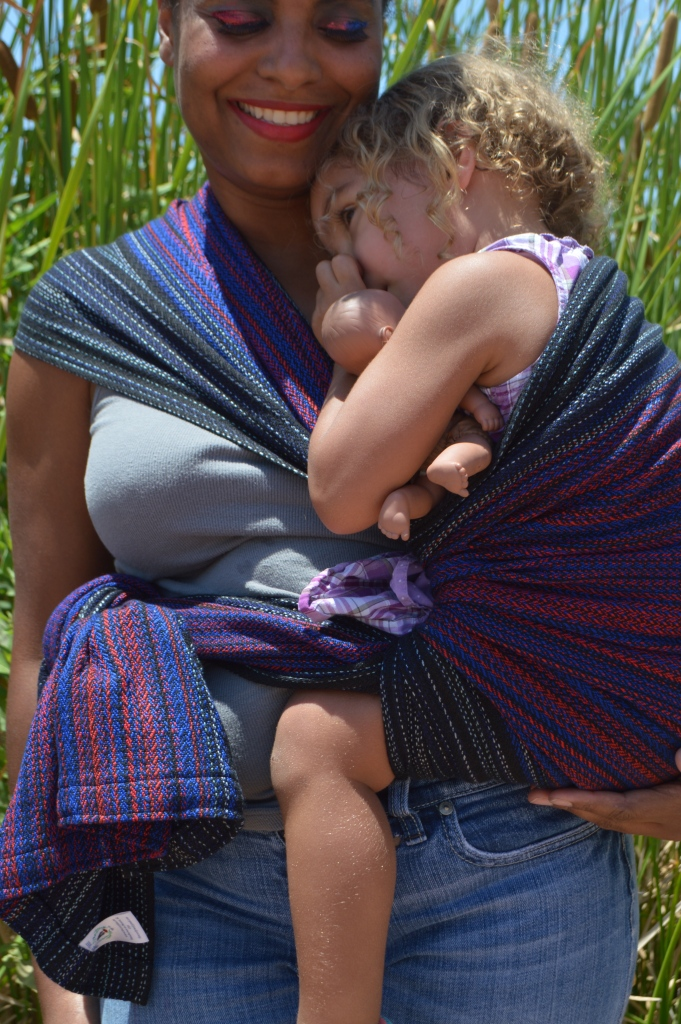 Image shows a medium brown african american momma cuddled close with light brown multiracial blond haired toddler in a Hip carry. They are standing in front of tall green reeds wearing a black red, and vibrant blue hand woven wrap. Baby is snuggled in close, thumb in mouth, heavy lidded ready for nap