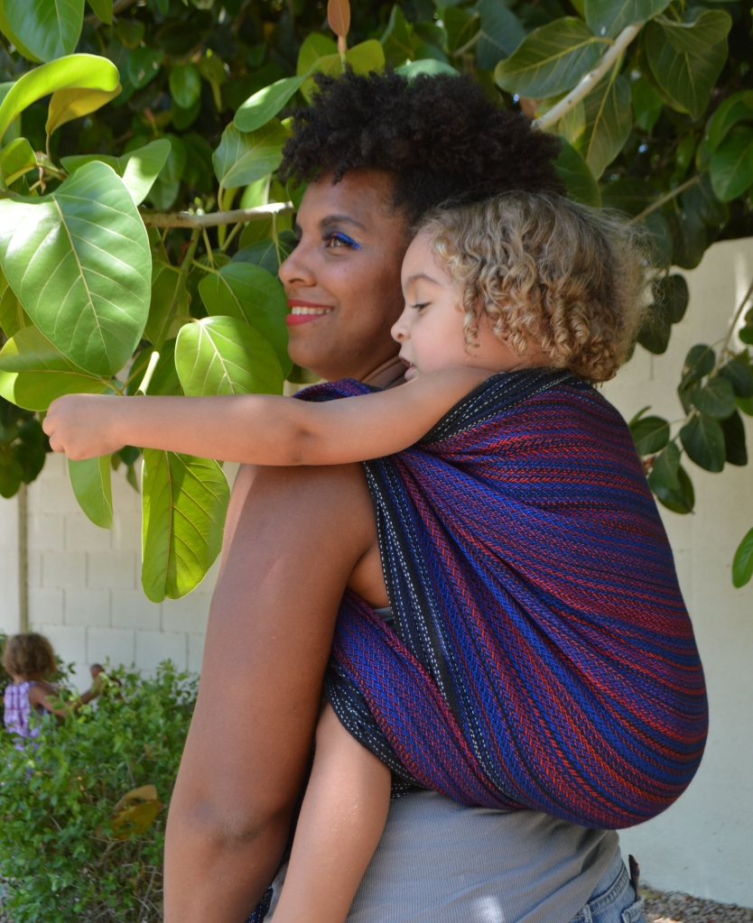 Image of a medium brown woman looking over her shoulder wearing a light brown, blond haired toddler on her back in a black, red, and blue wrap. Momma and baby are looking at leaf patterns in the trees above