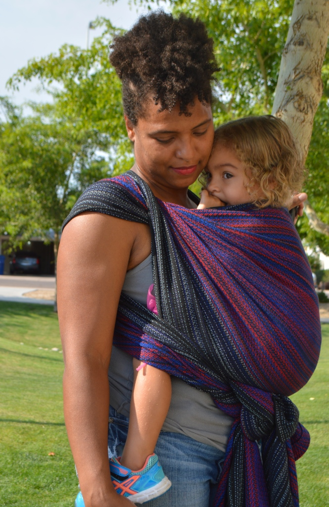 Image shows a medium brown african american momma cuddled close with light brown multiracial blond haired toddler in a front carry. They are standing in front of tall green reeds wearing a black red, and vibrant blue hand woven wrap. Baby is snuggled in close with thumb in her mouth