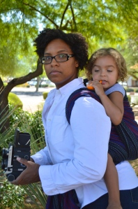 Image of a medium brown woman looking over her shoulder wearing a light brown, blond haired toddler on her back in a black, red, and blue wrap. The woman wears glasses and is dressed as Peter Parker in a white shirt holding a vintage Mamyia medium format camera