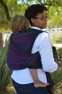Image of a medium brown woman looking over her shoulder wearing a light brown, blond haired toddler on her back in a black, red, and blue wrap. The woman wears glasses and is dressed as Peter Parker in a white shirt