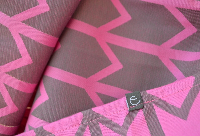 Close up image of a vibrant pink woven wrap with gray zig-zag pattern. The middle marker is present showing a stylized letter e