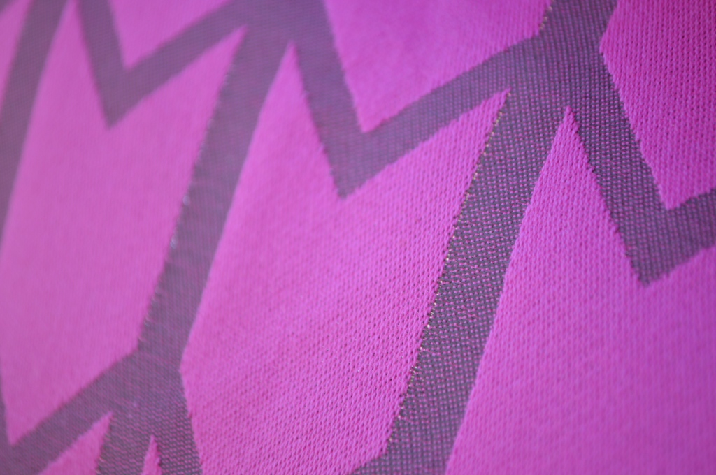 Very close up image showing the pink side of the wrap and a zoom in on one of the zig-zag stripes showing tiny little holes with light coming through