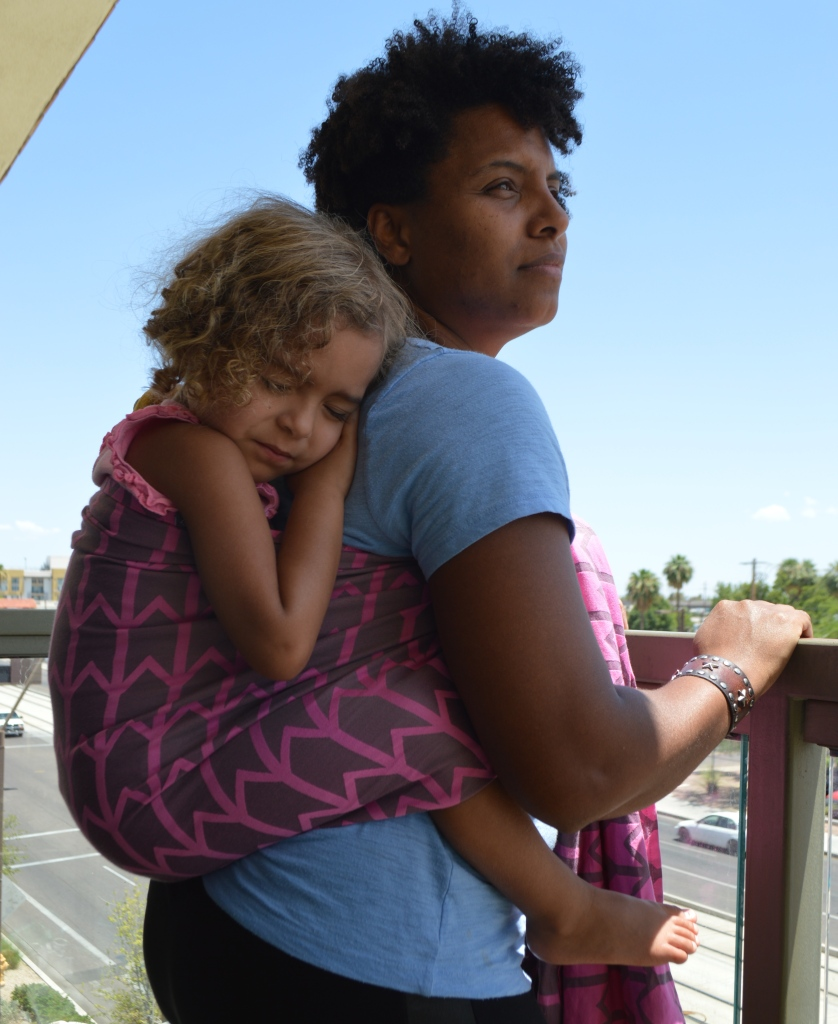 Image of a medium brown woman with natural curly hair staring off in the distance wearing a light brown toddler in a gray woven wrap with pink zig-zag pattern woven wrap