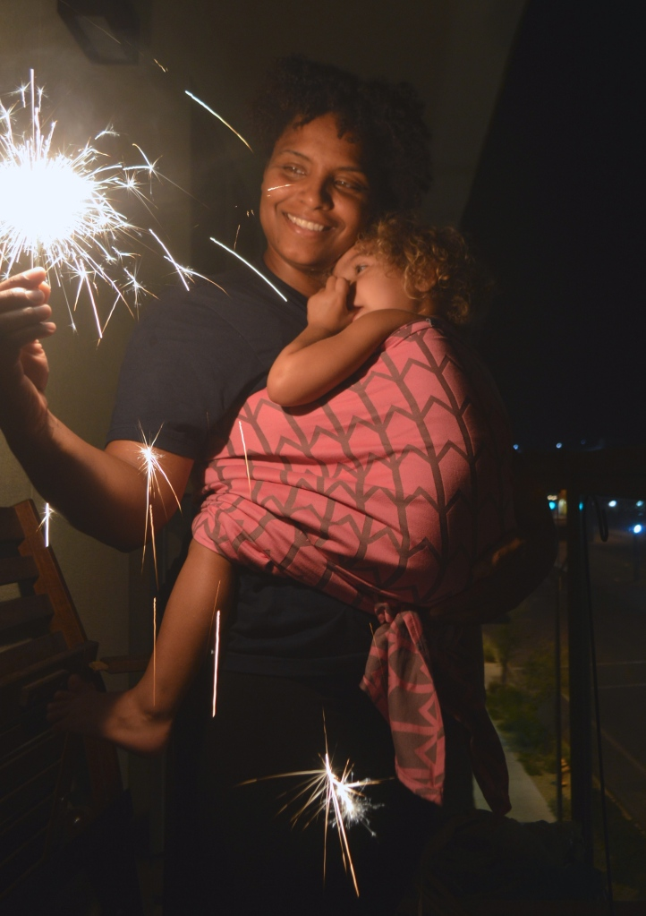 Image of a woman wearing a scared toddler in a front carry as they both look at the sparkler fizzling bright at night