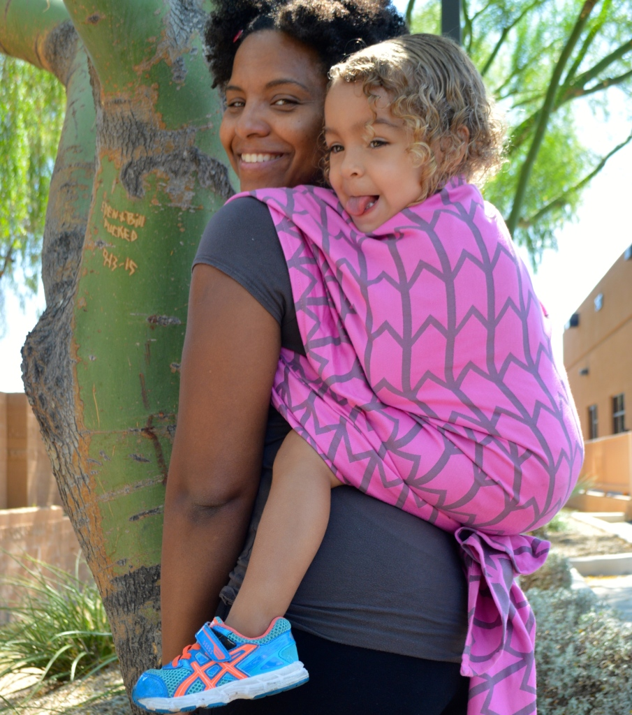 Image os a medium brown woman with natural hair wearing a light brown toddler with curly blonde air on her back in a vibrant pink woven wrap with gray zig-zag pattern