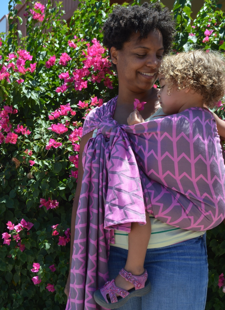 Image of a medium brown woman with natural curly hair wearing a light brown toddler with blonde hair in a gray woven wrap with pink zig-zag pattern. Momma is looking down at the toddler who is holding a hot pink flower