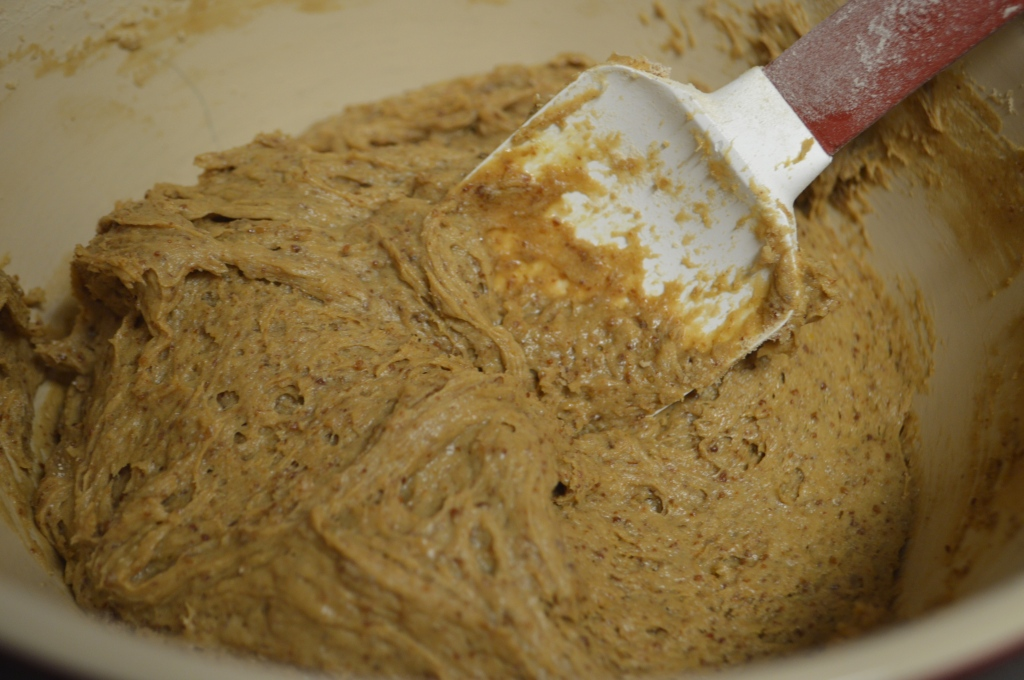 Image shows a light brown cookie dough in a ceramic bowl with a silicone spatula