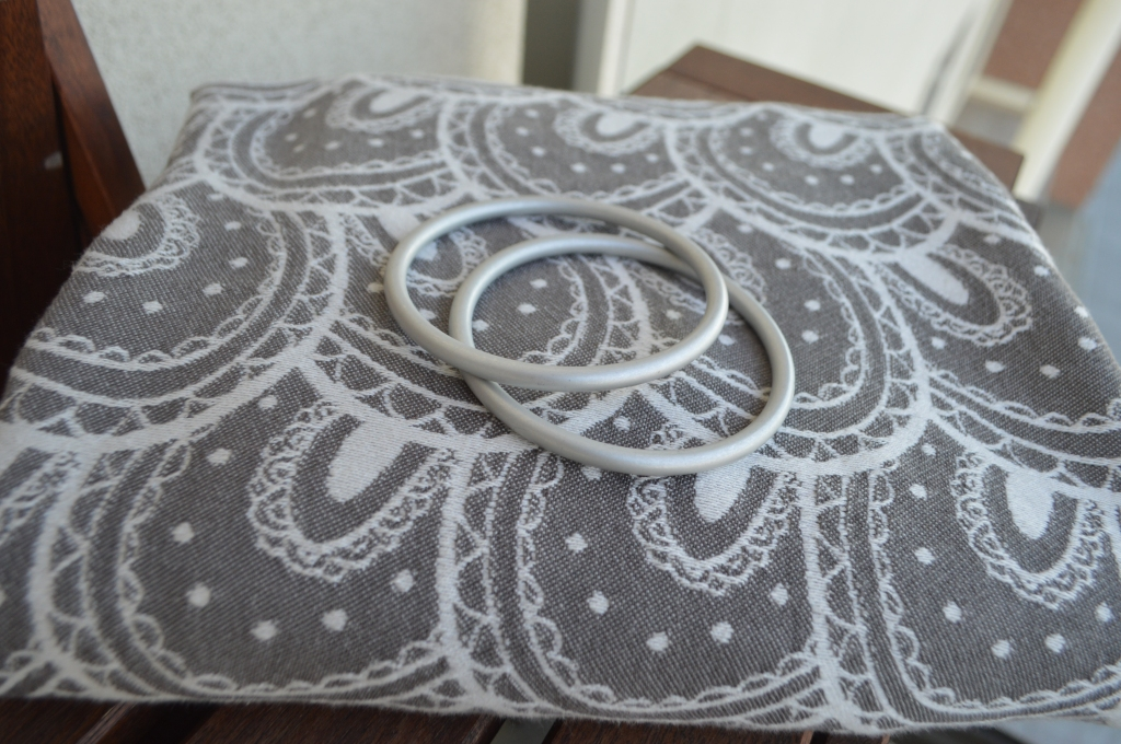 The image shows a gray and white woven wrap with repeating circular pattern neatly folded with two large silver aluminum sling rings on top