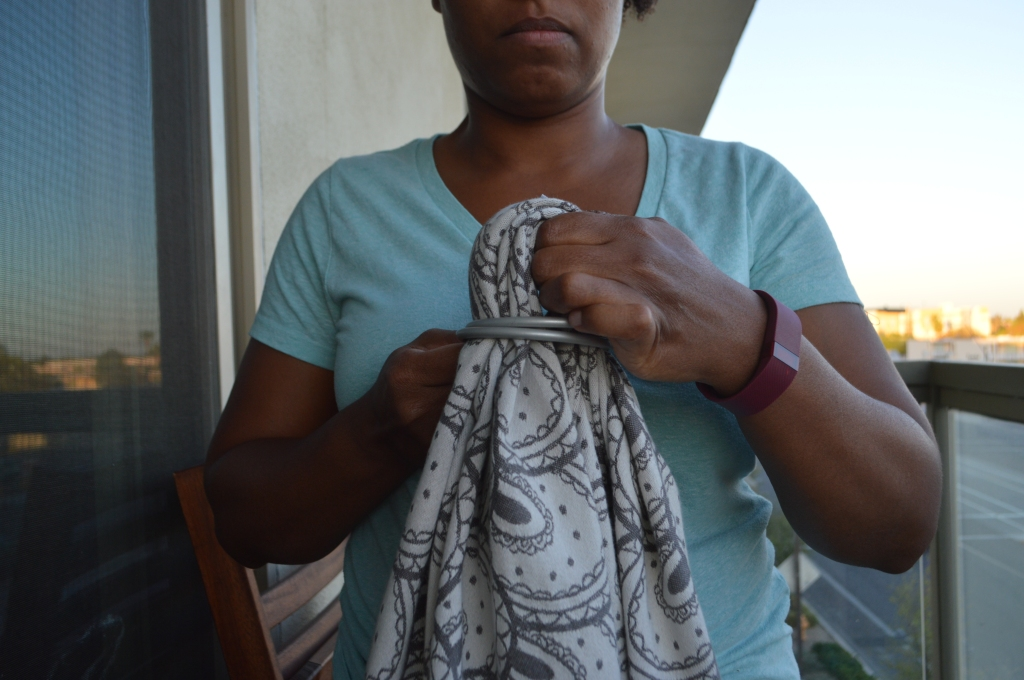 Image shows the brown skin woman feeding the looped wrap through both of the large silver aluminum sling rings